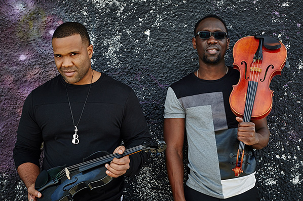 Black Violin holding their violins